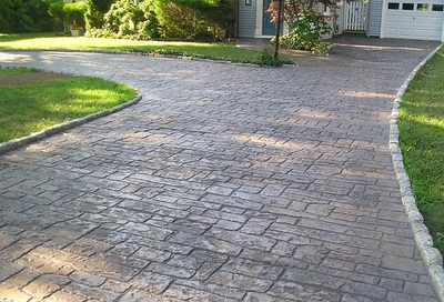 Long and bordered driveway stamped to look like brick pavers that are weathered.