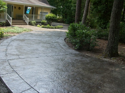 Dark stained concrete driveway that was stamped and sealed by Franklin Stamped Concrete.