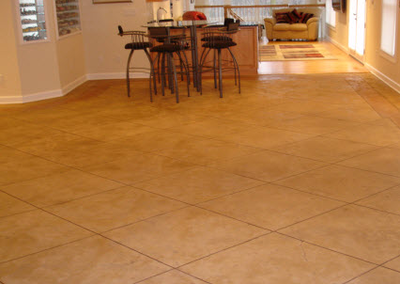 Main living floor that has square cut concrete which is stamped and stained to look like fancy tile.