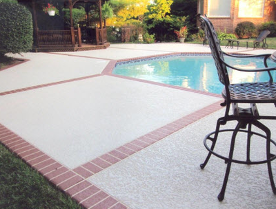 Concrete pool deck with stamped border that is stamped like brick pavers.