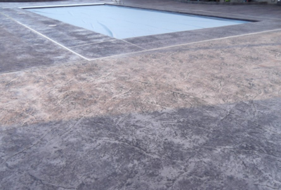 Gray stained concrete pool deck that is textured.