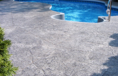 Built in pool with a textured gray pool deck.