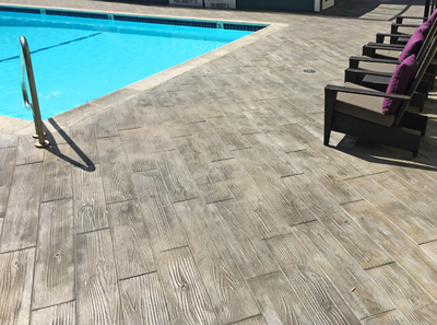 Awesome pool deck that is stamped and stained to resemble wood planks.