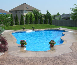 Pretty pool with a decorative concrete pool deck surrounding it.