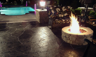 Gorgeous backyard patio with built in fire pit, adjacent to a built in pool.